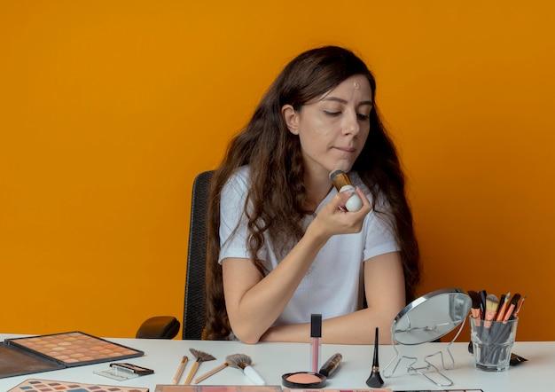 Junges hübsches mädchen, das an make-up-tabelle mit make-up-werkzeugen sitzt, die spiegel betrachten und fundament mit pinsel lokalisiert auf orange hintergrund anwenden