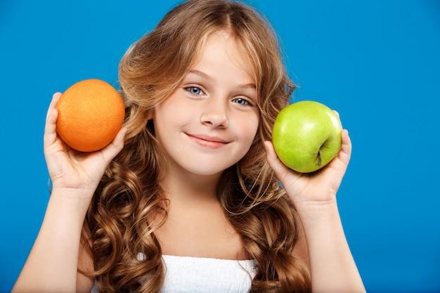Junges hübsches mädchen, das apfel und orange über blauer wand hält