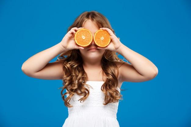 Junges hübsches mädchen, das augen mit orangen über blauer wand versteckt