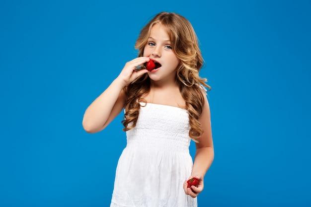 Junges hübsches mädchen, das erdbeere über blauer wand isst