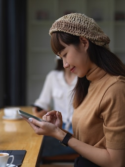 Junges hübsches mädchen, das ihr smartphone im bequemen arbeitsbereich verwendet