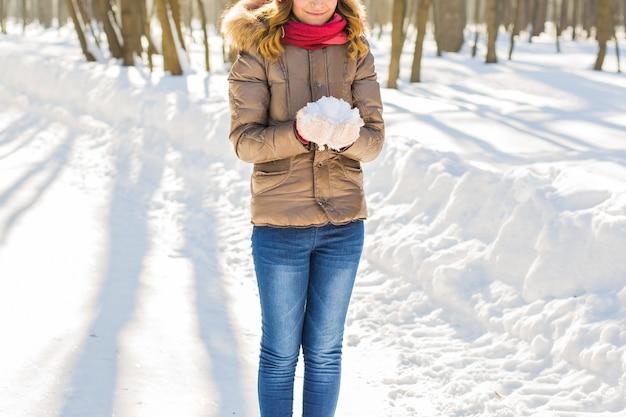 Junges hübsches mädchen, das schnee in den handschuhen hält.