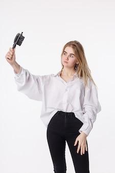 Junges hübsches mädchen, das selbstporträt mit smartphone auf kleinem stativ macht