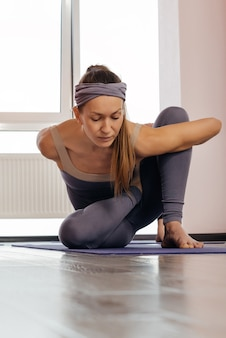 Junges hübsches mädchen, das yoga-pose in macht, frau, die yoga drinnen praktiziert