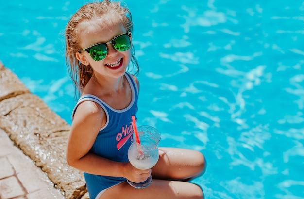 Junges hübsches mädchen im blauen bikini und in den sonnenbrillen, die nahe am pool mit cocktail sitzen und lächeln. speicherplatz kopieren.