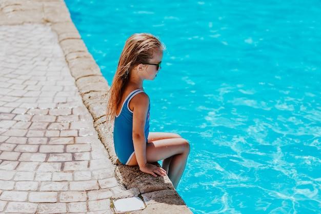 Junges hübsches mädchen im blauen bikini und in der sonnenbrille, die nahe am pool sitzen