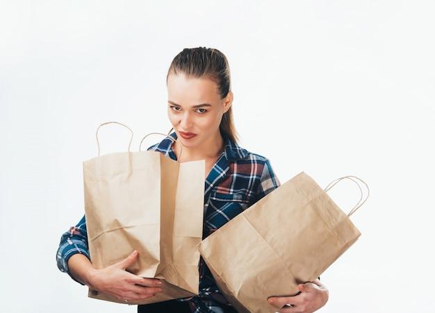 Junges hübsches mädchen im blauen hemd mit vollen einkaufstaschen in ihren händen