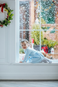 Junges hübsches mädchen im blauen winterkleid und in den strumpfhosen, die nahe dem großen fenster mit weihnachten sitzen.