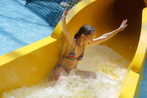 Junges hübsches mädchen in einem gestreiften bunten badeanzug lacht, reitet auf einer gelben wasserrutsche im aquapark.