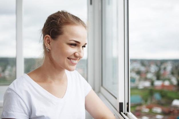 Junges hübsches mädchen in einem weißen t-shirt steht am fenster auf dem balkon auf dem hintergrund des stadtbildes
