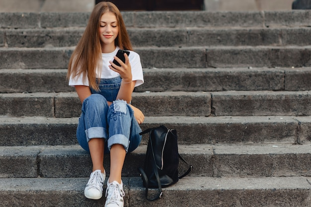 Junges hübsches mädchen mit dem aktenkoffer, der auf treppe sitzt und sms am telefon schreibt