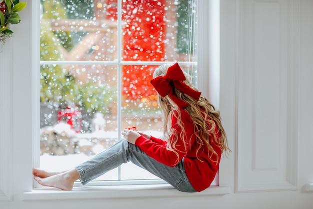 Junges hübsches mädchen mit dem langen blonden lockigen haar mit der roten weihnachtsschleife und dem winterpullover, die auf dem großen fenster mit schneiendem hintergrund sitzen.