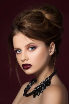 Junges hübsches mädchen mit dunkelrotem lippenstift und schwarzer halskette, die aufwirft