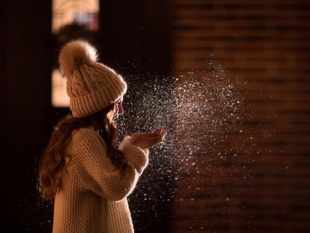 Junges hübsches mädchen mit langen haaren in der weißen wintermütze und im pullover, die schnee bei nachtterrasse blasen.