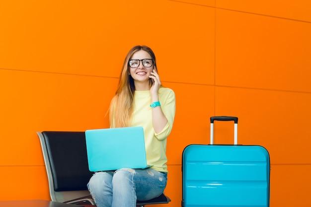 Junges hübsches mädchen mit langen haaren sitzt auf stuhl auf orange hintergrund. sie trägt einen gelben pullover, jeans und eine brille. sie hat einen blauen laptop auf den knien und einen koffer. am telefon sprechen.