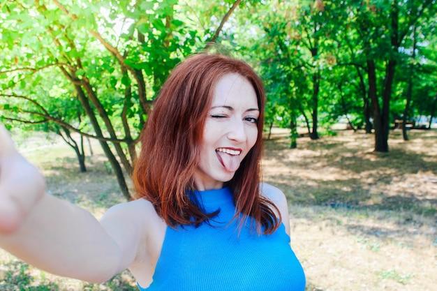 Junges hübsches mädchen mit roten haaren macht im sommer ein selfie auf ihrem handy.