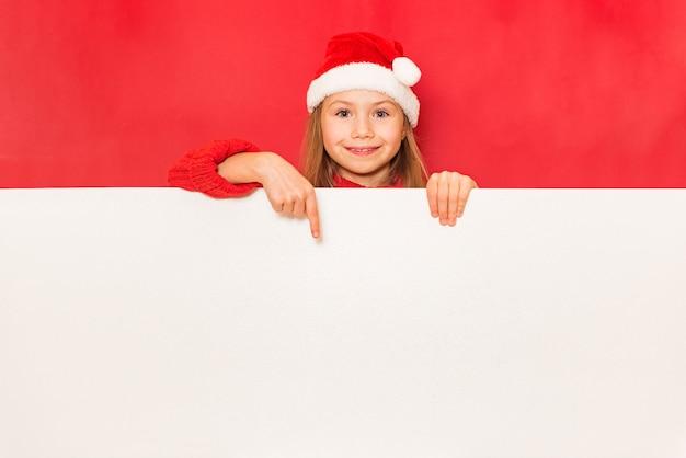 Junges hübsches mädchen mit weißer leerer fahne auf rotem hintergrund
