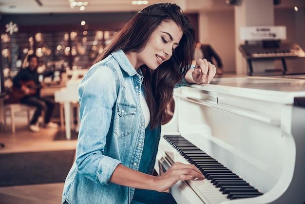 Junges hübsches mädchen spielt klavier im musikgeschäft.