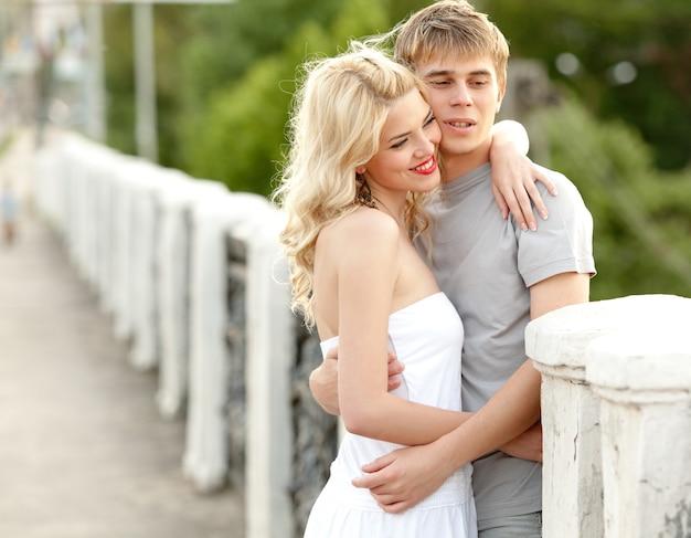 Junges hübsches paar charmantes mädchen in einem weißen kleid und ein mann geht auf der brücke an einem warmen sommer sonnigen tag. konzept der romantischen spaziergänge