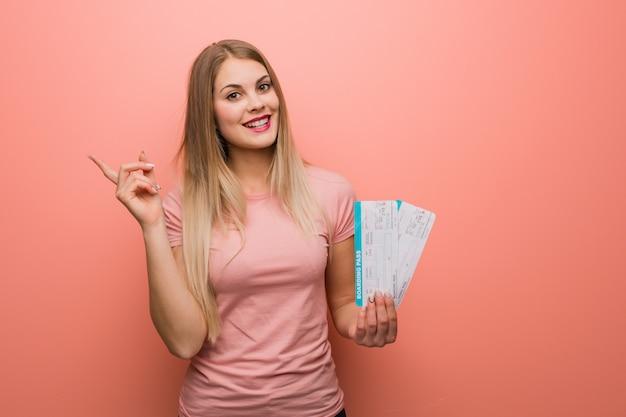 Junges hübsches russisches mädchen, das auf die seite mit dem finger zeigt. sie hält tickets.