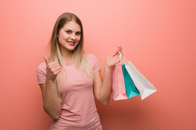 Junges hübsches russisches mädchen, das oben daumen lächelt und anhebt. sie hält eine einkaufstüte.