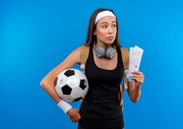 Junges hübsches sportliches mädchen, das stirnband und armband und rückentasche mit kopfhörern am hals trägt, die flugtickets mit fußball halten und seite betrachten