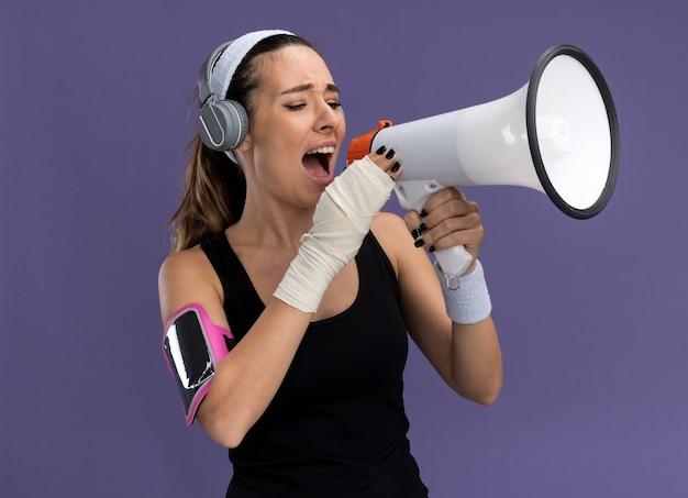 Junges hübsches sportliches mädchen mit stirnband-armband-kopfhörern und telefon-armband mit verletztem handgelenk, das mit verband umwickelt ist und über lautsprecher spricht, die auf lila wand isoliert ist