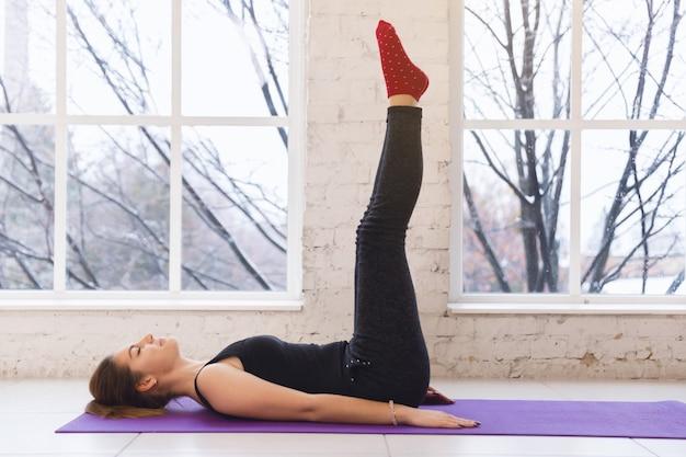 Junges hübsches sportliches yogamädchen liegen auf dem boden mit den beinen oben