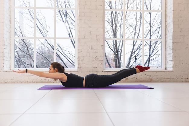 Junges hübsches sportliches yogamädchen liegen auf dem boden mit der hand und den beinen oben. asana shalabhasana