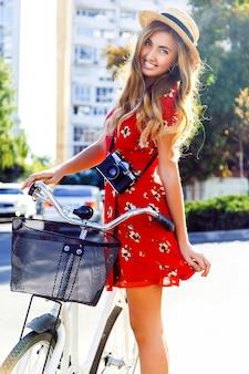 Junges hübsches stilvolles blondes fotografmädchen, das im hellen blumenkleid mini und im strohhut aufwirft