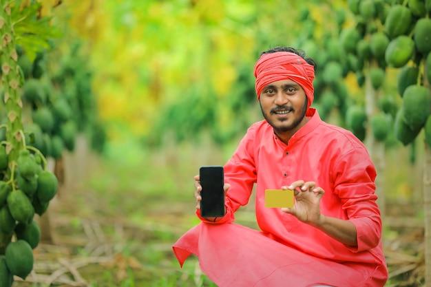 Junges indisches kind, das handybildschirm am papaya-feld zeigt