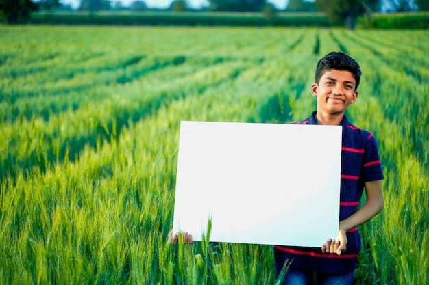 Junges indisches kind mit leerem plakat am indischen weizenfeld