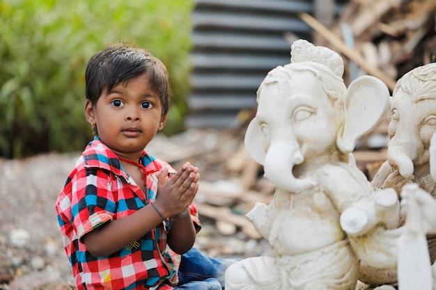 Junges indisches kind mit lord ganesha