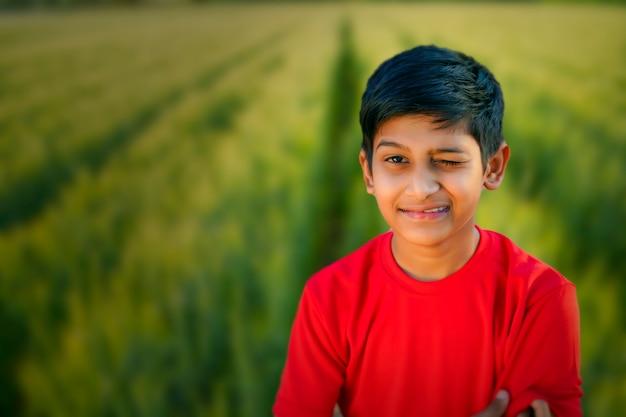 Junges indisches kind zwinkert seinem auge zu