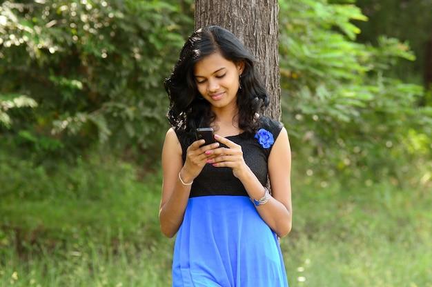 Junges indisches mädchen, das ein handy oder smartphone im park im freien verwendet