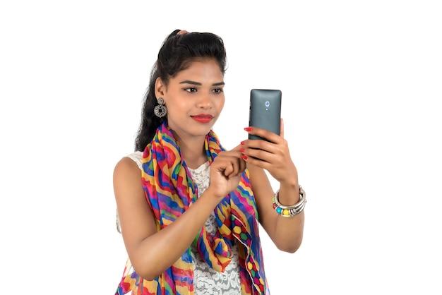 Junges indisches mädchen, das ein handy oder smartphone lokalisiert auf einem weißen hintergrund verwendet