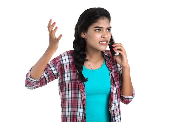 Junges indisches mädchen, das ein mobiltelefon oder smartphone lokalisiert auf einer weißen wand verwendet