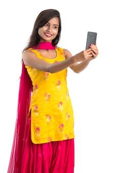 Junges indisches mädchen, das eine tablette, ein mobiltelefon oder ein smartphone lokalisiert auf einem weiß verwendet
