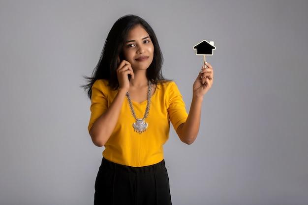 Junges indisches mädchen, das handy oder smartphone benutzt und kleines brett auf grau zeigt.