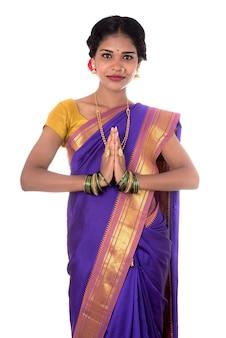 Junges indisches mädchen in traditioneller kleidung, das namaste begrüßt, willkommen, indisches mädchen in einem traditionssari mit willkommenem ausdruck (einladend)