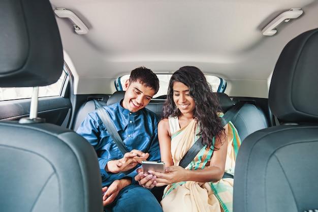 Junges indisches paar mit handy auf dem rücksitz eines autos
