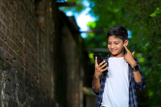 Junges indisches süßes kind mit smartphone