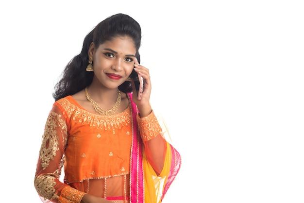 Junges indisches traditionelles mädchen, das ein handy oder smartphone auf weiß verwendet