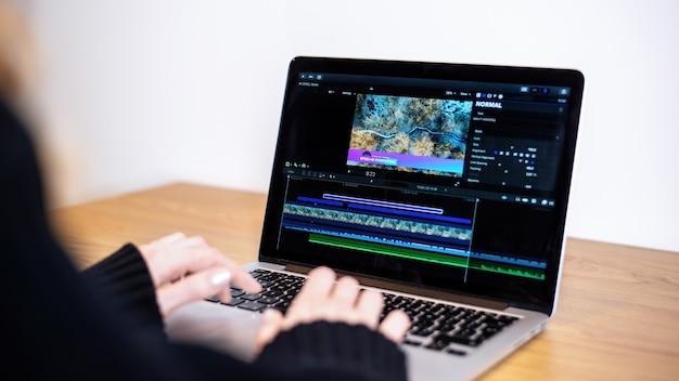 Junges inhaltsschöpfermädchen, das video auf ihrem laptop bearbeitet. von zu hause aus arbeiten