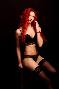 Junges intimes rothaariges frauenschönheitsporträt in dessous gegen schwarzen hintergrund.