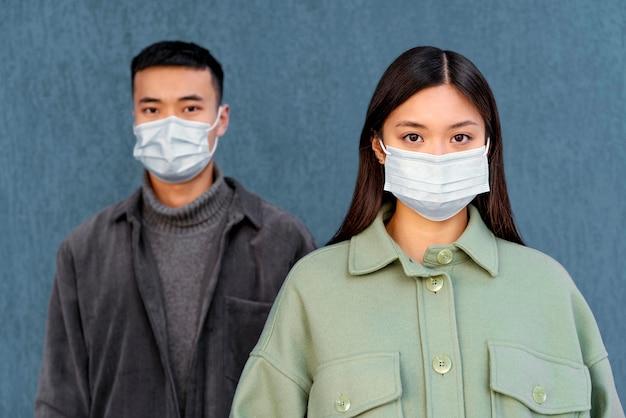 Junges japanisches paar, das maske trägt