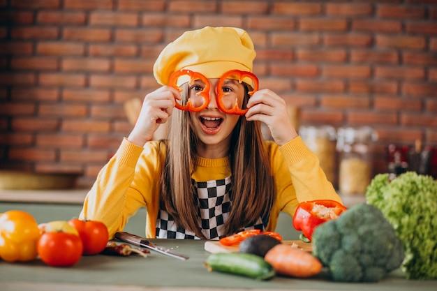 Junges jugendlich mädchen, das salat für frühstück in der küche vorbereitet