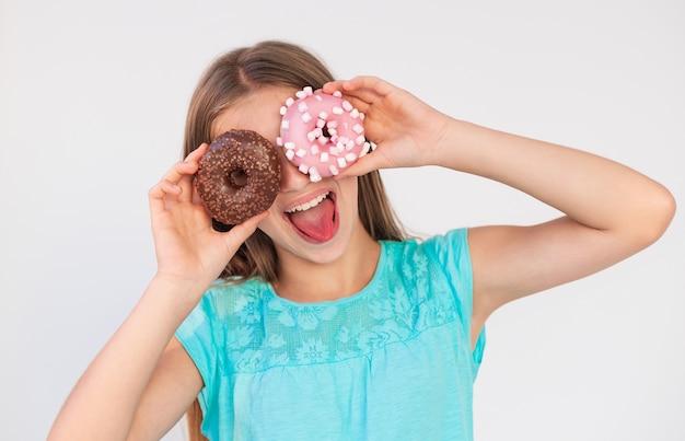 Junges jugendlich mädchen mit einem verspielten ausdruck setzt einen donuts zu ihren augen