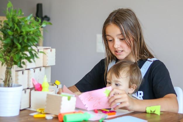 Junges jugendliches mädchen mit ihrem kleinen bruder, der papiergrußkarte schafft