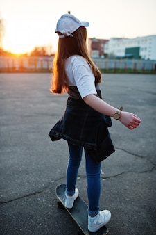 Junges jugendliches städtisches mädchen mit skateboard, abnutzung auf gläsern, kappe und zerrissenen jeans am yard-sportplatz.